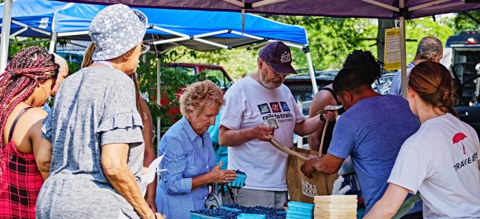 customers at a farm stand at a farmers market