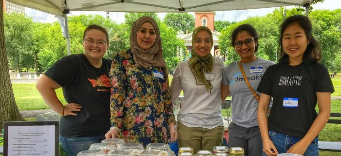 5 women behind of a farm stand at a farmers market