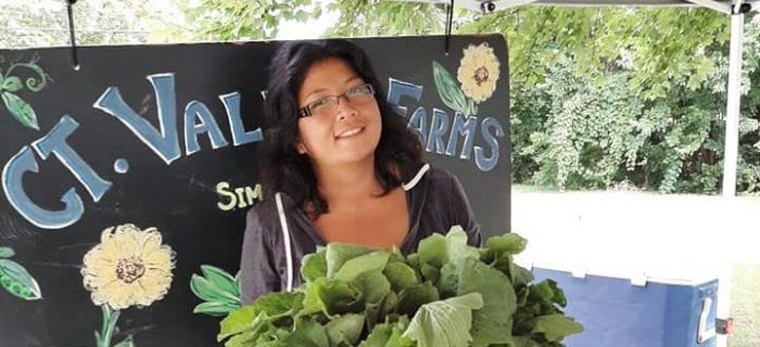 woman in front of sign holding a tub of greens