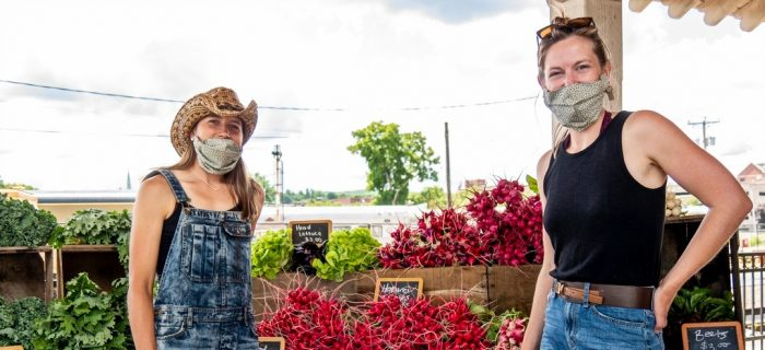 Two female farmers in front of a farmstand full of veggies