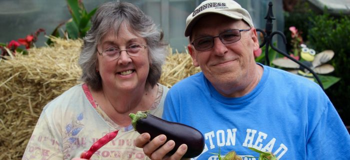 Man and Woman holding a crate full of veggies