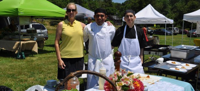 two cooks with woman and a basket of fresh produce and flowers