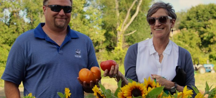 man and woman holding tomatoes with sunflowers in front of them