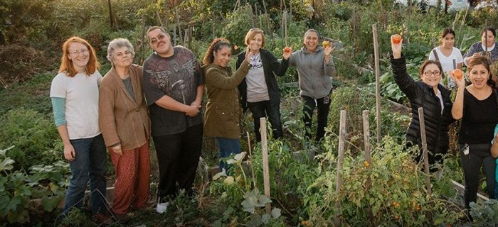 group of people holding tomatoes in a garden