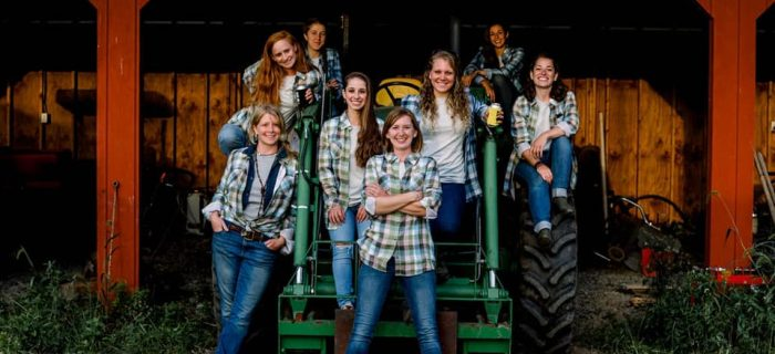 8 female farmers sitting on a tractor