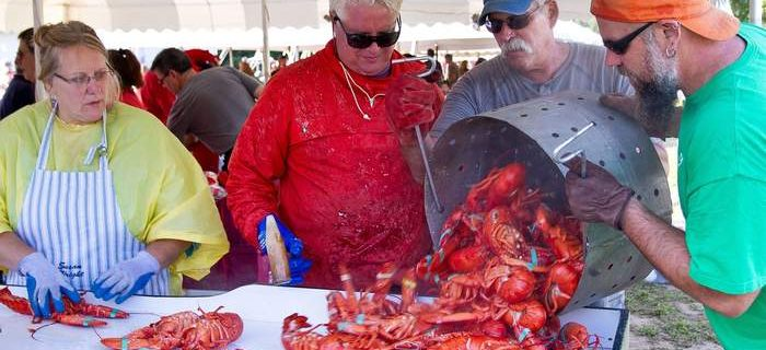 man pouring big pot of lobsters on a counter