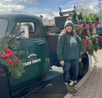 Farmer in front of an old fashioned truck decorated with wreaths