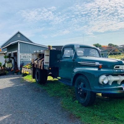 Old truck in front of a farmstand