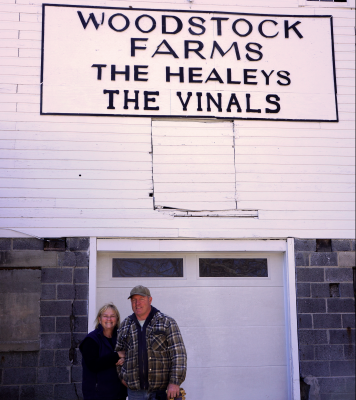 man and woman in front of farm sign